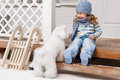 Girl with a dog on the front porch little white sunny winter day Royalty Free Stock Image
