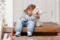 Girl with a dog on the front porch little white sunny winter day Royalty Free Stock Photos