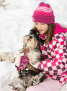 Girl with dog in lap hugs her on snow during winter walk nature Royalty Free Stock Photography