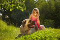Girl with dog little large in the garden Stock Photography