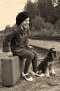 Girl with dog retro laughing little sitting on a suitcase on the railroad his Stock Photo