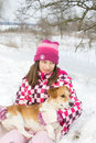 Girl and dog on snow hugs her during winter walk in nature Stock Image