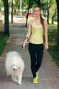 Girl with a dog for a walk white walks in the park Royalty Free Stock Image