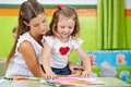 Girl doing arts and crafts with mother in nursery room Stock Photography