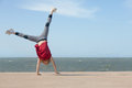 Girl doing cartwheel little by the ocean Stock Photos