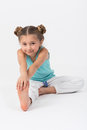 Girl doing gymnastics exercise sitting on the floor Stock Photo