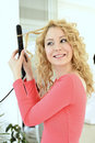 Girl doing hairstyle with flat iron Royalty Free Stock Photo