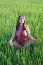 Girl doing yoga against grass Royalty Free Stock Photo