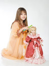 Girl and doll studio photo holding a on a light background Royalty Free Stock Photography