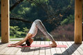 Girl in downward facing dog pose nice is engaged yoga on the wooden terrace on the nature background she stands sideways the on Stock Images