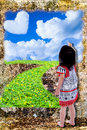 Girl draw nature with paintbrush on grunge wall background. Royalty Free Stock Photo