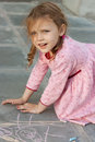 Girl with drawing with chalks little outdoors Stock Photos