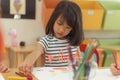 Girl drawing color pencils in kindergarten classroom, preschool and kid education concept. Royalty Free Stock Photo