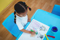Girl drawing in her colouring book at the desk Royalty Free Stock Photos