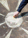 Girl drawing a sun with colored chalk on pavement street Royalty Free Stock Image