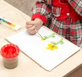 A girl draws a drawing with paints on a sheet Royalty Free Stock Photo