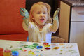 Girl draws little paints children s hands at the table Stock Photos