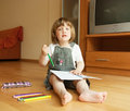 Girl draws little while sitting on floor Royalty Free Stock Image