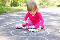 Girl draws a sun little large on asphalt Stock Images