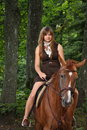 Girl in dress and brown horse portrait in forest summer Stock Image