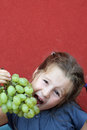 Girl with dress eating white grapes blue a bunch of Stock Image