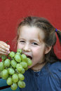 Girl with dress eating white grapes a bunch of Royalty Free Stock Images