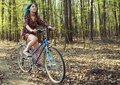 stock image of  The girl in the dress rides a bicycle through the forest.