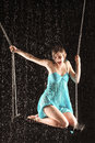 Girl in dress seat on bent legs on swing Stock Photography