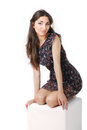 Girl in dress sitting on a cube posing studio Stock Photography