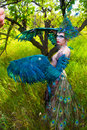 A girl dressed as a bird fever wearing firebird for show against the backdrop of nature on sunny day Royalty Free Stock Photos
