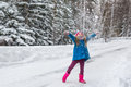 Girl dressed in a blue coat and a pink hat and boots throws snow up Royalty Free Stock Photo