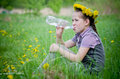 Girl drink water with dandelions in meadow Stock Image