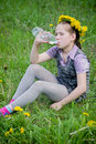 Girl drink water with dandelions in meadow Royalty Free Stock Photo