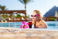 Girl drinking coctail in the pool small Royalty Free Stock Photos