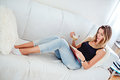 Girl drinking coffee and reading book on the sofa Royalty Free Stock Photo