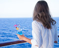 Girl drinking a cold drink admiring the sea views summer Royalty Free Stock Images