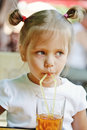 Girl drinking juice small beautiful from straw Royalty Free Stock Photo