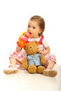 Girl drinking juice toddler with teddy bear from bottle and sitting down on floor Royalty Free Stock Images