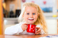 Girl drinking milk in kitchen child cup or mug of the domestic Stock Images
