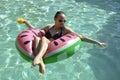 Girl drinking orange juice on watermellon float