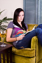 Girl Drinking while Reading a Book Royalty Free Stock Image