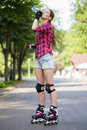 Girl drinking water in park with her blades on beautiful is drinkin a while she wears rollerblades Stock Photography