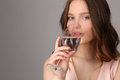 Girl drinking water from a wine glass. Close up. Gray background Royalty Free Stock Photo