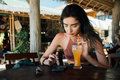 Girl drinks juice and checks the phone cafe on vacation with a view of the sea and the beach. Royalty Free Stock Photo