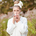Girl drinks tea pretty young in retro clothes enjoying autumn day Stock Photo