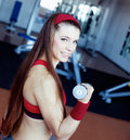 Girl with dumbbell in fitness club Stock Image