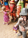 Girl and dwarfs colorful wood sculptures of dwarf or gnome figures with a cute little admiring them Stock Image