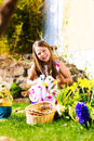 Girl on Easter egg hunt with living Easter Bunny Stock Photos