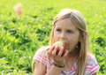 Girl eating an apple little kid hairy blond Royalty Free Stock Photos