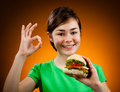 Girl eating big sandwich showing OK sign Stock Image